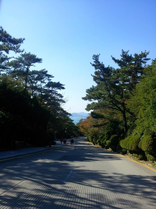 Saat jalanan mulai mendaki, terlihat lautan dan gunung di kejauhan